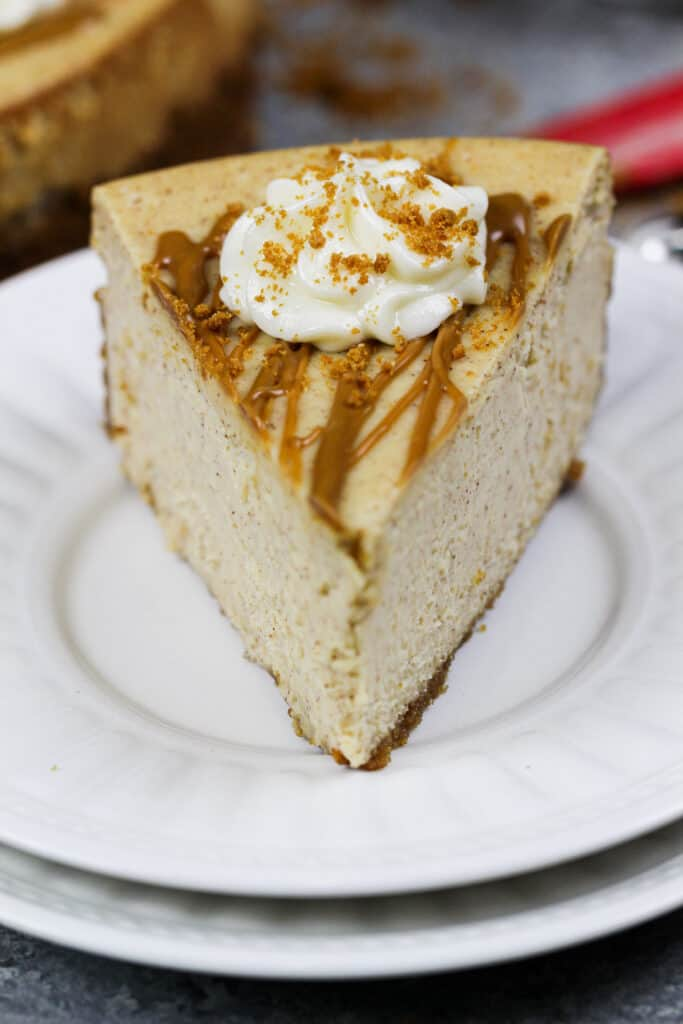image of a slice of biscoff cheesecake drizzled with cookie butter and topped with whipped cream