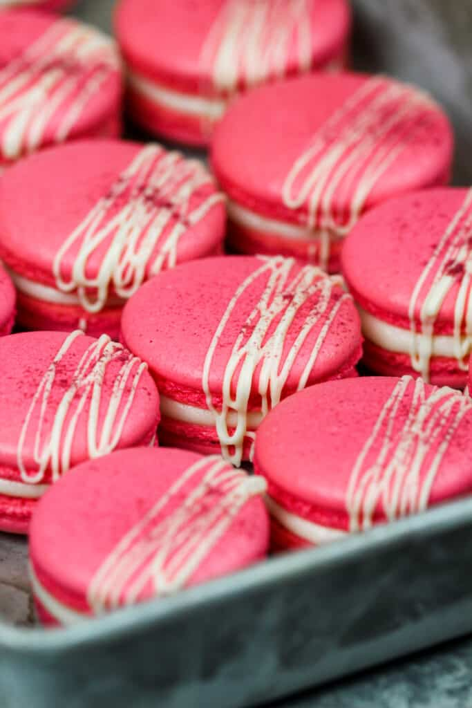 image of raspberry french macarons drizzled with white chocolate and dusted with raspberry powder