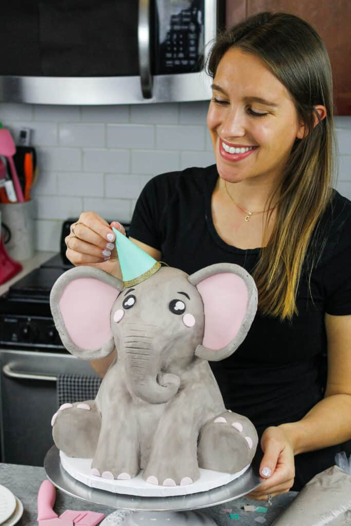 image of an elephant cake being made for a baby shower with a party hat