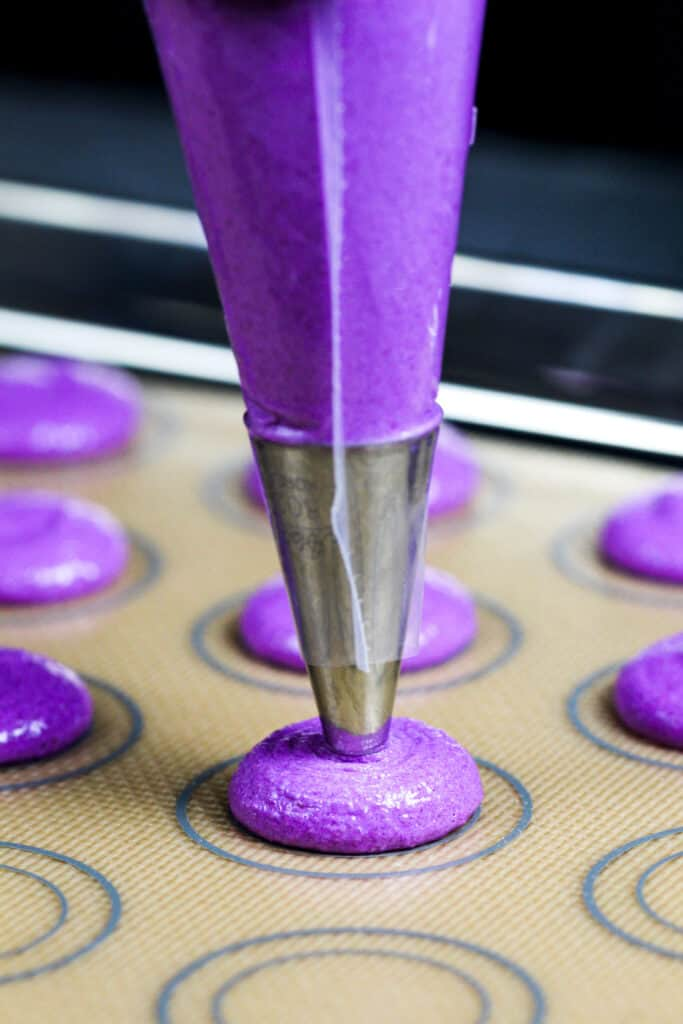 image of purple macarons being piped onto a silpat mat