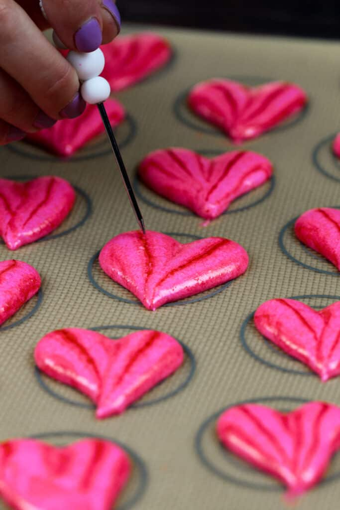 image of heart shaped macaron shells that have been piped and are resting