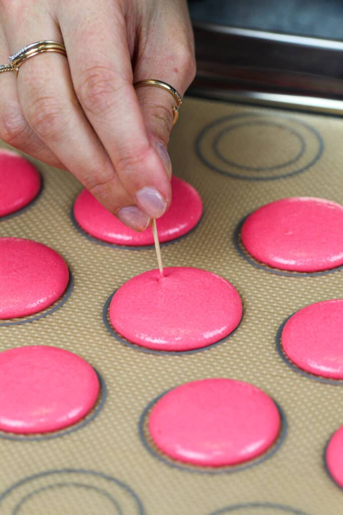 image of pink macaron shells that've been piped and are having their air bubbles popped with a toothpick
