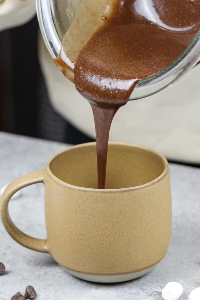 image of chocolate cake batter being poured into a mug to make a hot cocoa mug cake in the microwave