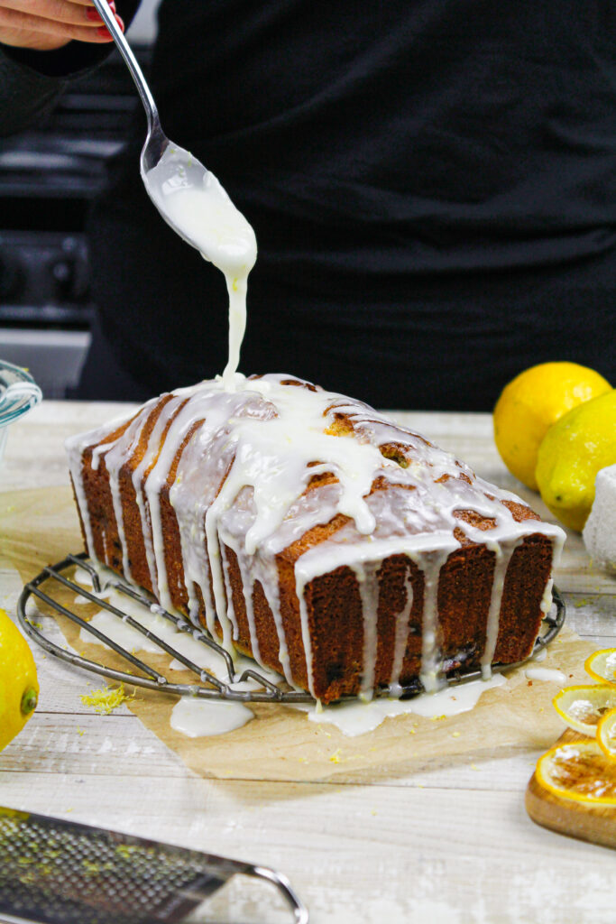 image of lemon glaze being drizzled over a blackberry loaf