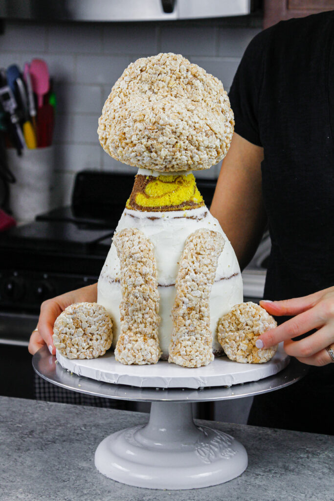 image of a giraffe cake being made with marble cake layers and cake decorating rice krispies