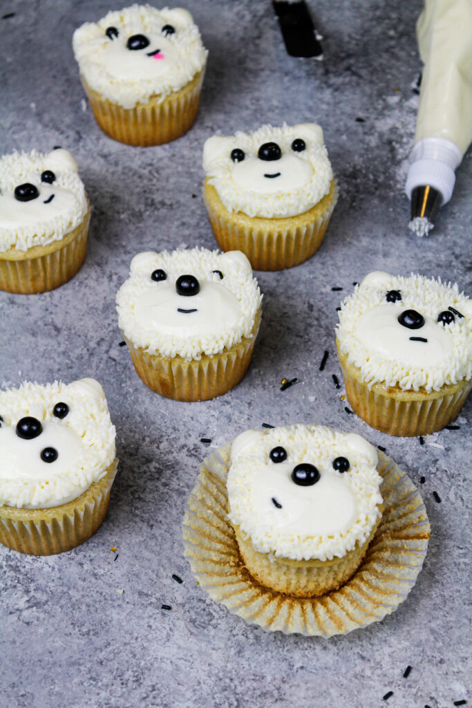 image of an easy polar bear cupcakes made with buttercream frosting and black sprinkles