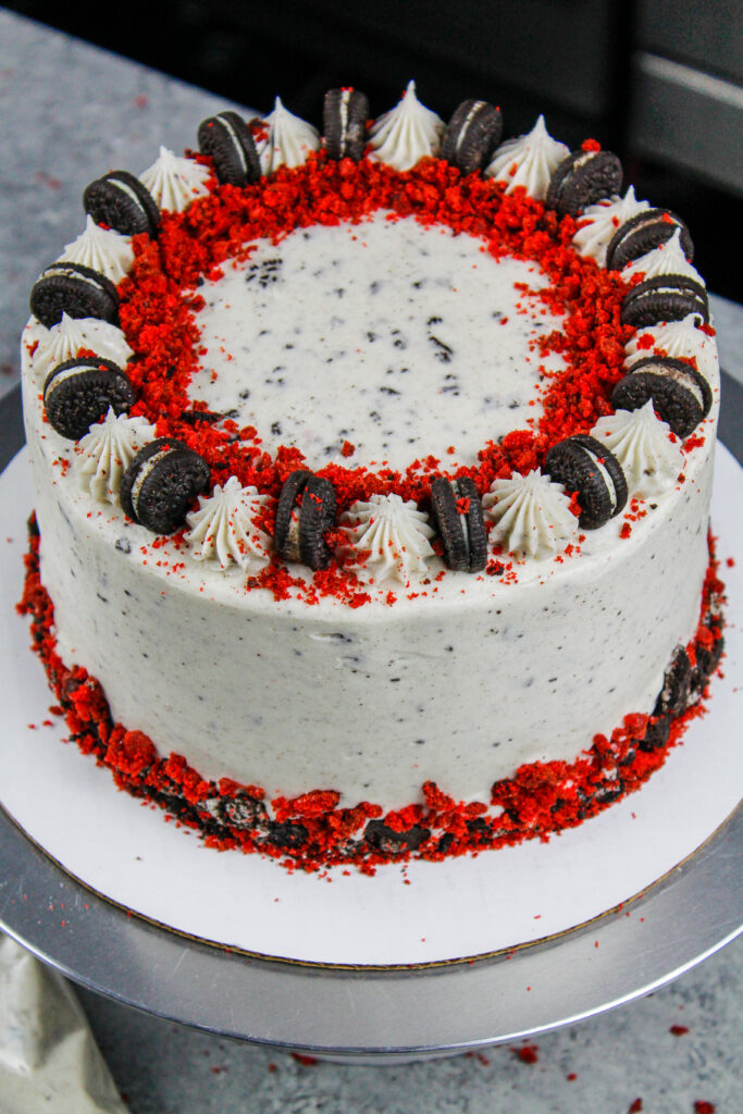 image of a red velvet oreo cake decorated with crushed oreos and red velvet cake crumbs
