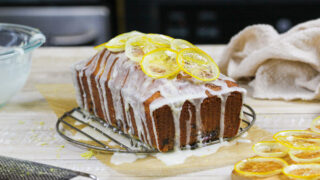 image of a blackberry lemon bread drizzled with lemon glaze and topped with candied lemons