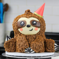 image of a sloth birthday cake made with chocolate cake layers and chocolate peanut butter buttercream