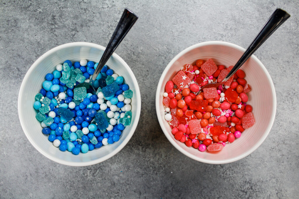 image of pink and blue candy and sprinkles ready to be used to fill a surprise inside cake for an exciting gender reveal party
