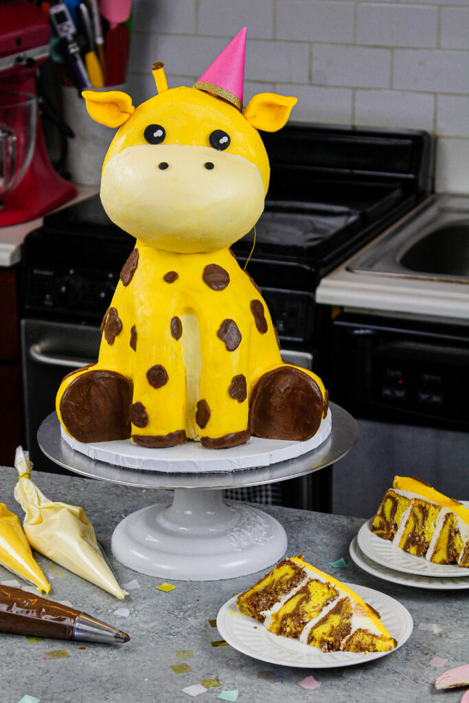 image of a cute giraffe birthday cake that's been cut into to show its yellow marble cake layers
