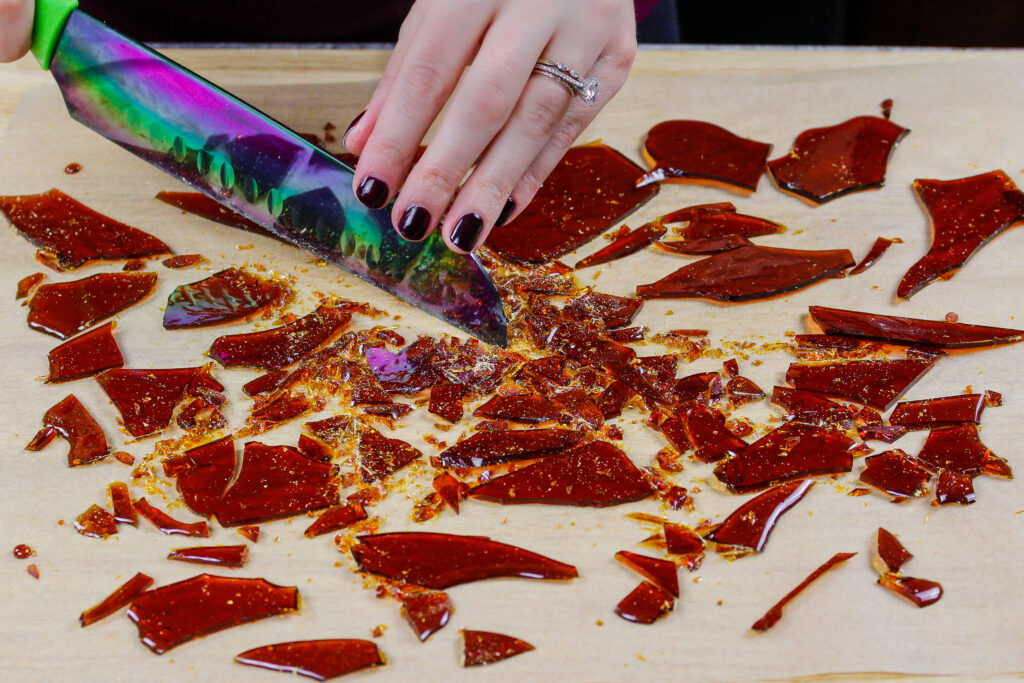 image of caramelized sugar shards being cut into small pieces using a sharp knife