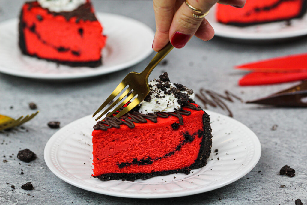 image of a slice of red velvet oreo cheesecake decorated with melted chocolate, whipped cream and crushed oreos