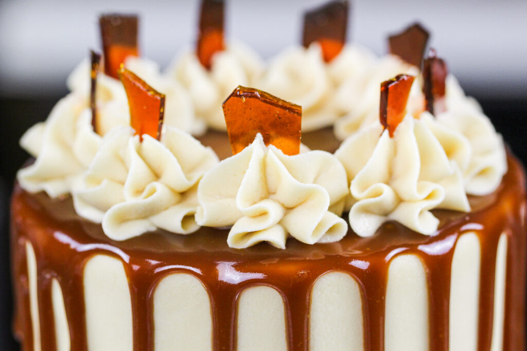 image of the top of a 4-inch caramel brown sugar drip cake decorated with caramel buttercream swirls and caramelized sugar shards
