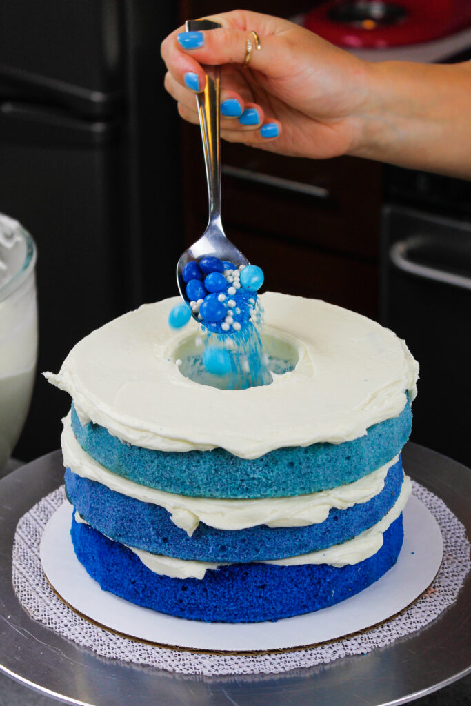 image of a blue ombre cake being filled with blue candy and sprinkles for a boy gender reveal cake