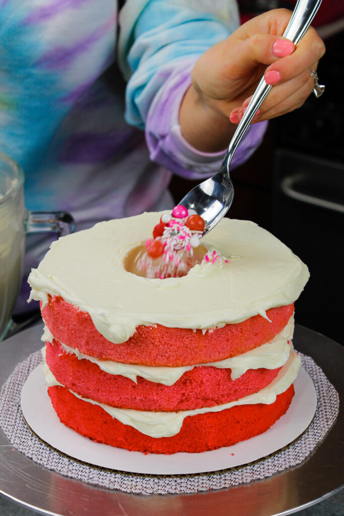 image of a blue ombre cake being filled with pink candy and sprinkles for a girl gender reveal cake