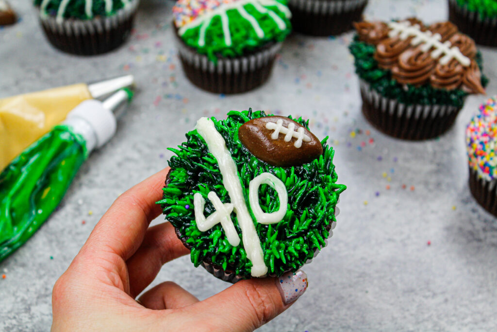 image of a football cupcake decorated to look like a yard line with a tootsie roll football