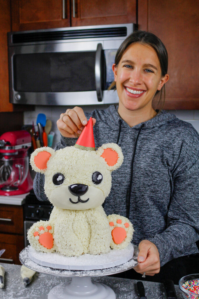 image of chelsey white of chelsweets putting a party hat on her polar bear cake, which was made as part of her animal cake series