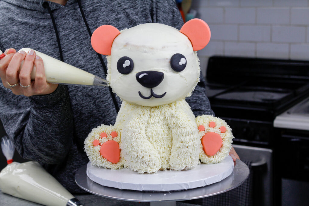 image of polar bear cake being covered in buttercream fur using a small grass tip