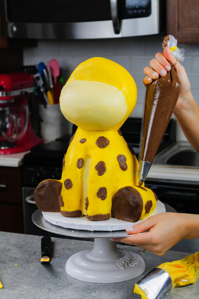 image of a giraffe cake that is having its spots piped on using chocolate buttercream