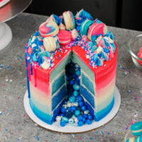 image of a gender reveal cake decorated with ombre cake layers and a surprise inside sprinkle and candy filling