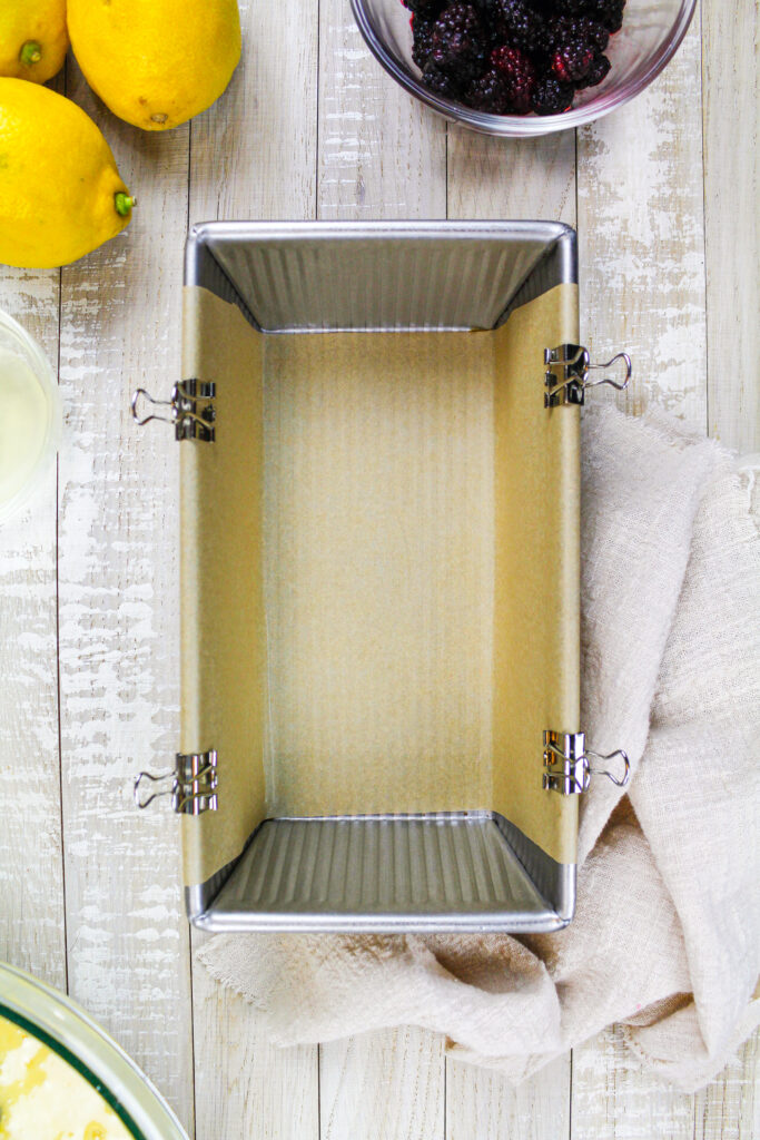 image of a loaf pan greased with non-stick spray and lined with a sling of parchment paper that's secured with metal binder clips