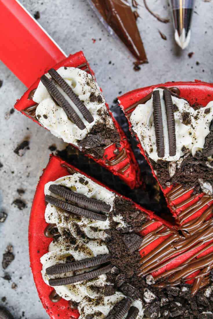 image of red velvet oreo cheesecake that's been cut and is having a slice pulled out to be eaten