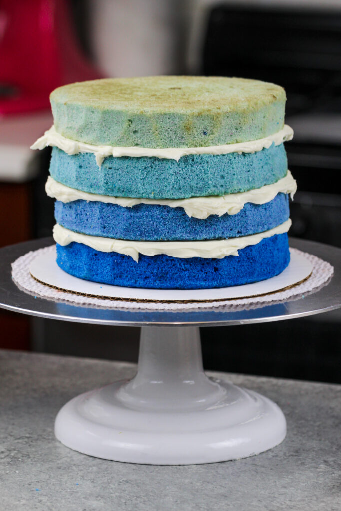 image of ombre blue cake layers stacked and frosted with american buttercream