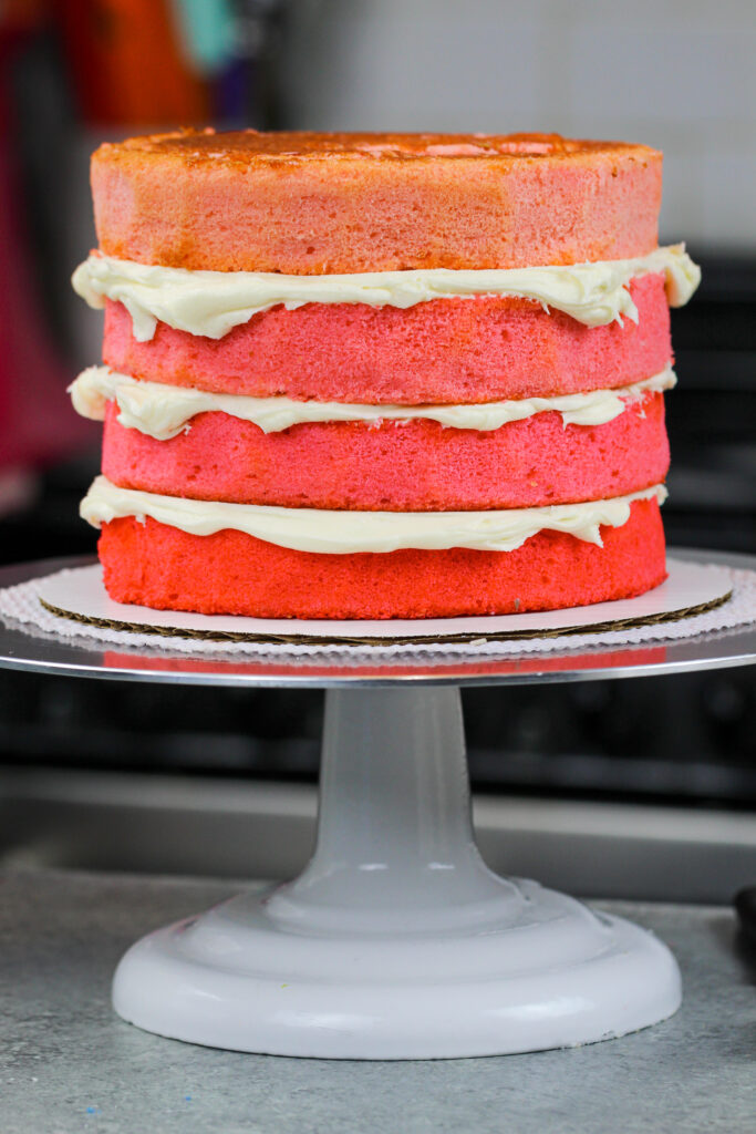 image of ombre pink cake layers stacked and frosted with american buttercream