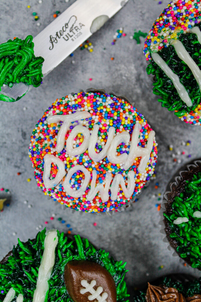image of a football cupcake decorated with white buttercream and sprinkles to say touchdown