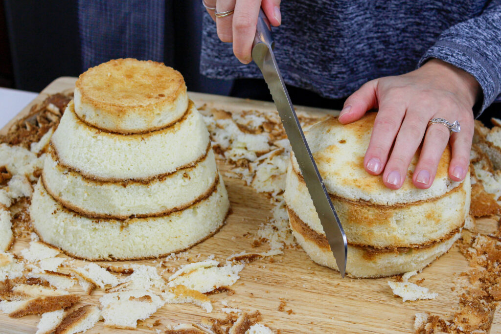 image of fluffy vanilla cake layers being trimmed down to make a polar bear shaped cake
