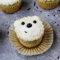 image of adorable polar bear cupcakes made with buttercream frosting and black sprinkles
