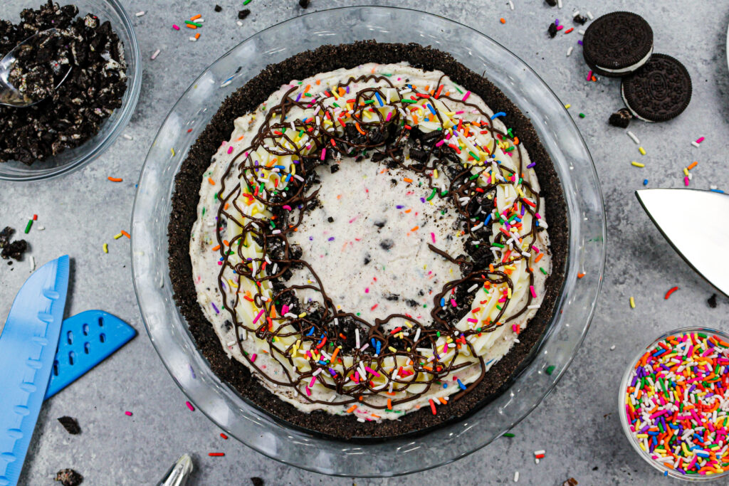 image of an oreo cream pie decorated with sprinkles and buttercream