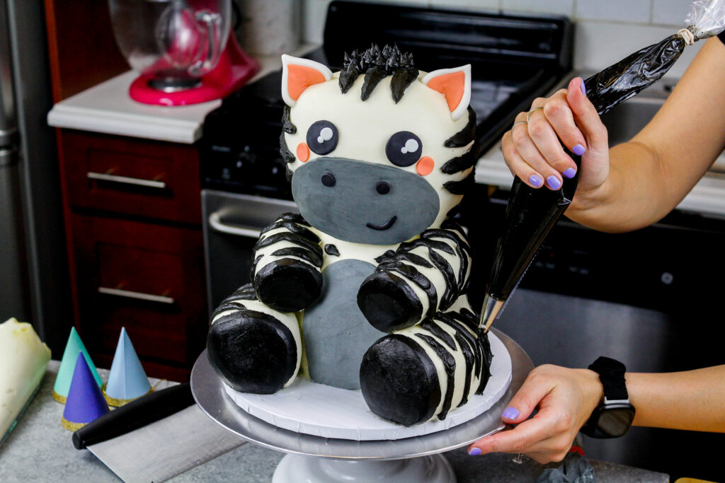 image of black buttercream frosting stripes being piped onto an adorable baby zebra cake made for a birthday party