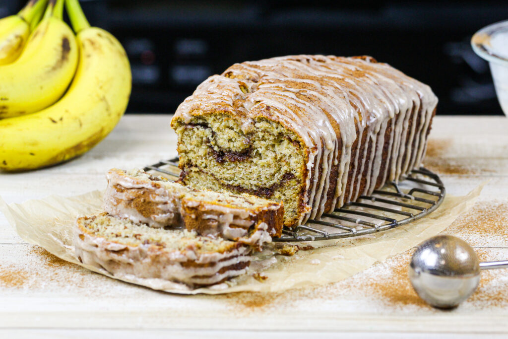 image of cinnamon swirl banana bread loaf that's been sliced into to show its beautiful cinnamon sugar swirls
