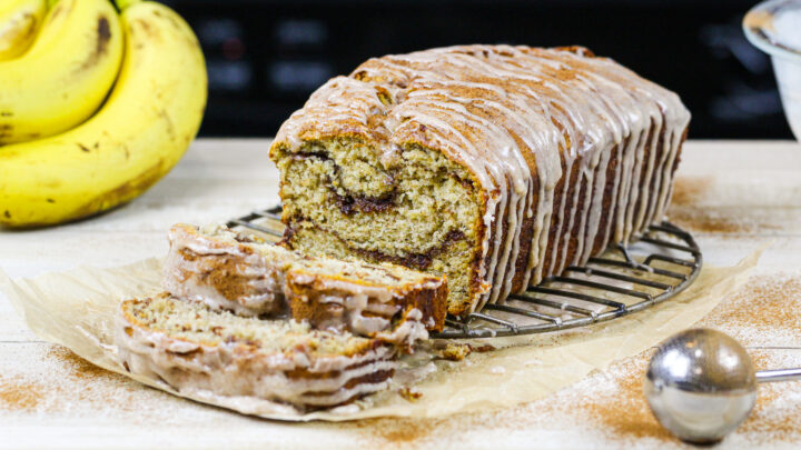 image of cinnamon swirl banana bread loaf that's been sliced into to show its beautiful cinnamon sugar swirls