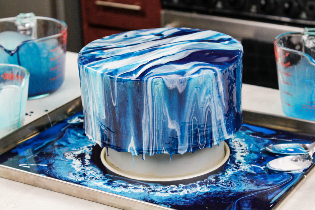 image of an ocean inspired white and blue mirror glaze cake