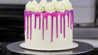 image of a purple drip cake made with a colorful white chocolate ganache