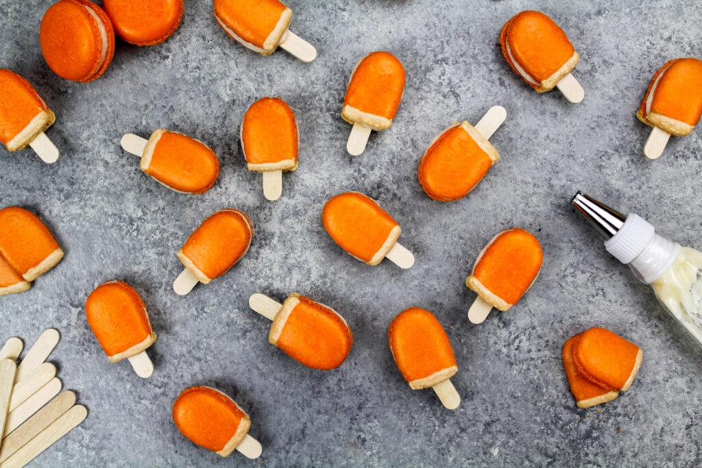 image of mini orange creamsicle macarons filled with orange creamsicle buttercream