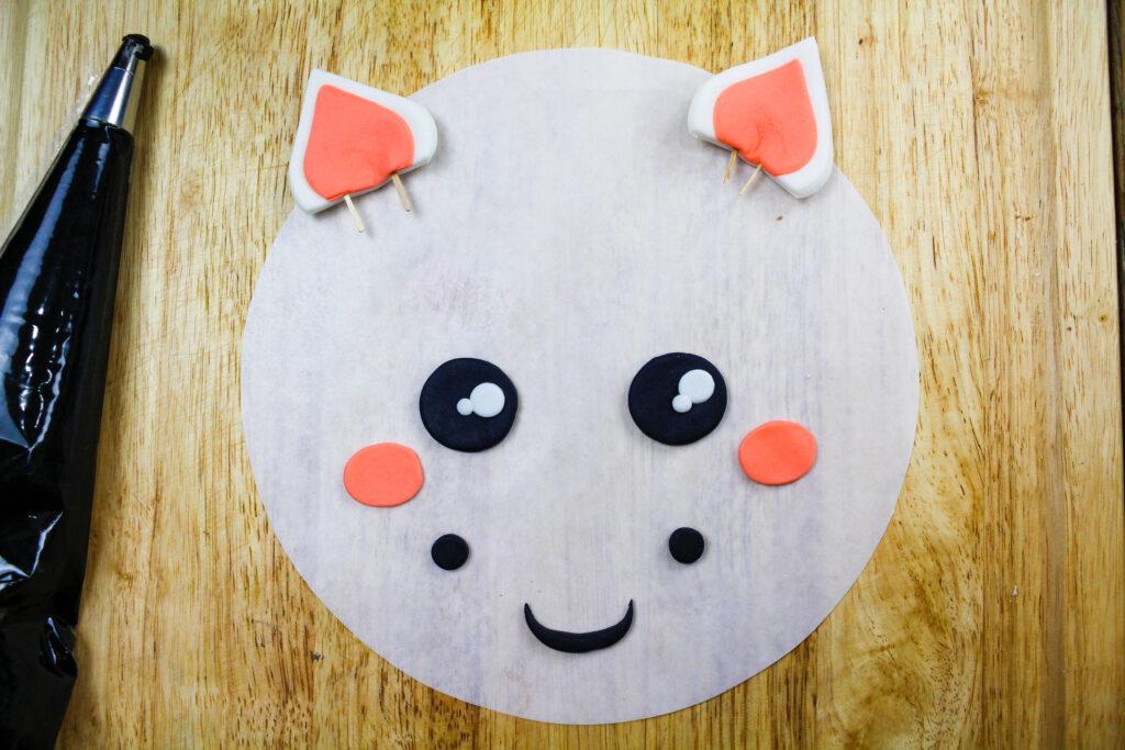 image of a cute fondant face made for a zebra cake