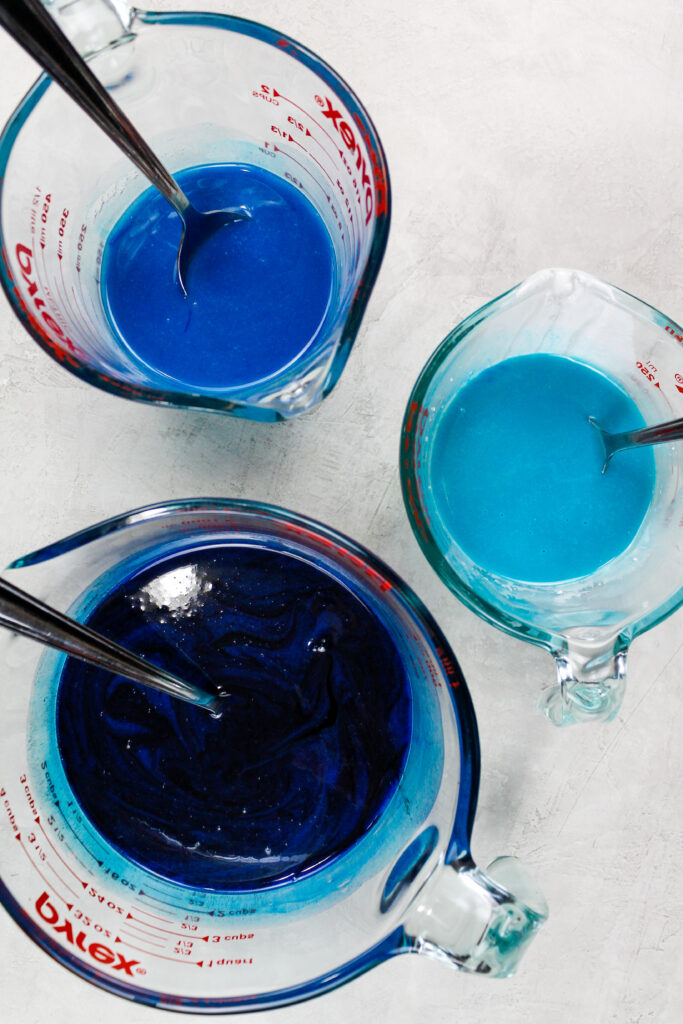 image of three shades of blue mirror glaze ready to be used to make an ocean themed cake