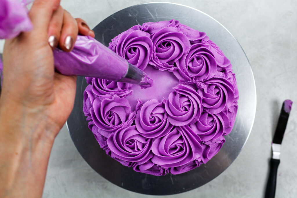 image a of a purple buttercream rosette being piped onto a cake
