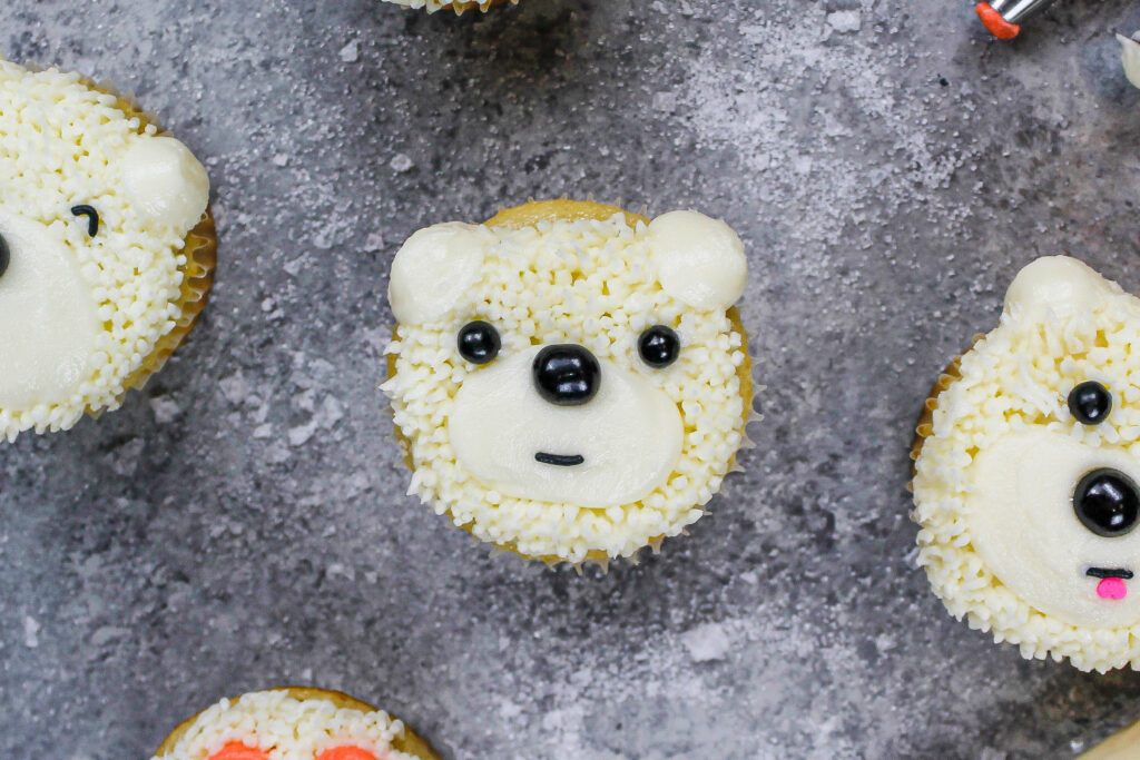 image of a polar bear cupcake being made with buttercream and black sprinkles for the face