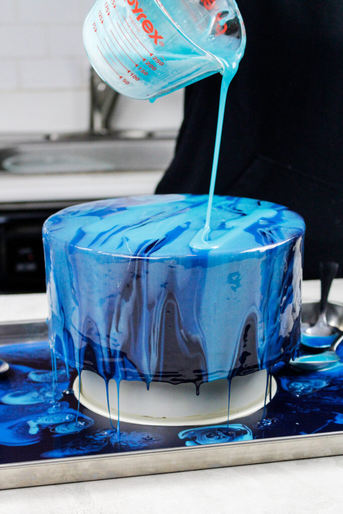 image of blue mirror glaze being poured over a chilled buttercream cake