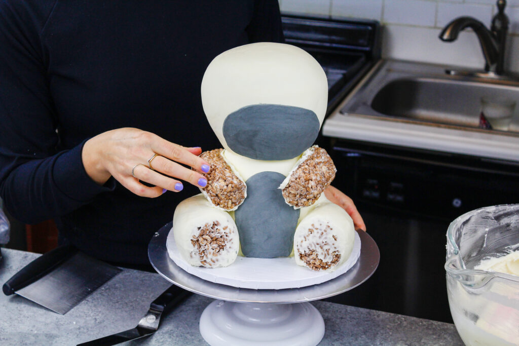 image of cake decorating rice krispies being added to a zebra cake to make it's legs and arms