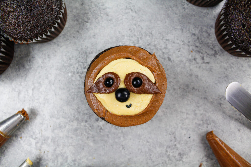 image of an adorable sloth cupcakes made with chocolate cupcake being decorated with chocolate peanut butter frosting
