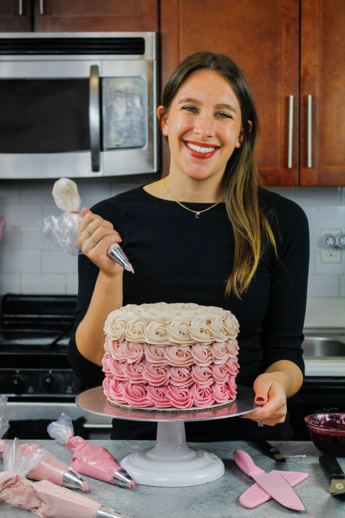 image of chelsey white of chelsweets piping a pink ombre rosette cake