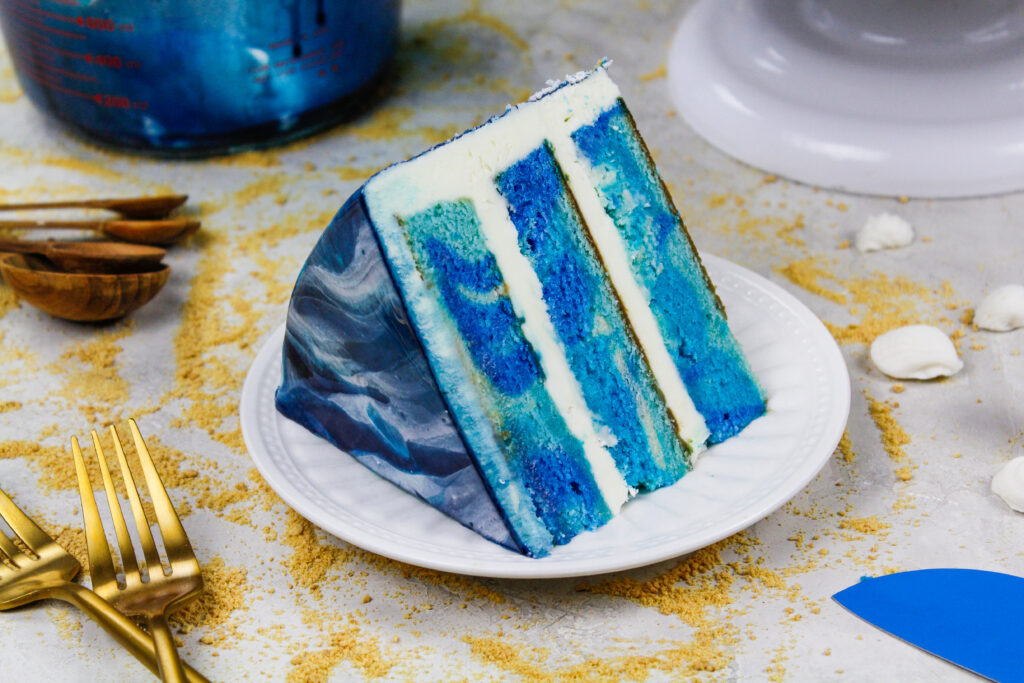 image of an ocean themed cake made with blue swirled cake layers and a pretty blue and white mirror glaze