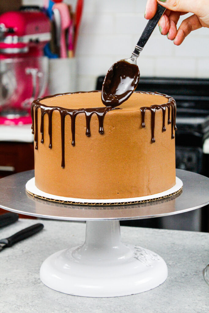 image of chocolate ganache drips being added to a chocolate drip cake with a spoon