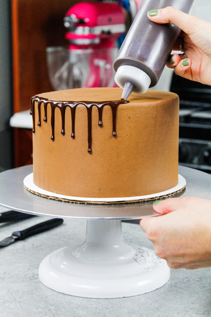 image of chocolate ganache drips being added to a chocolate drip cake using a plastic bottle